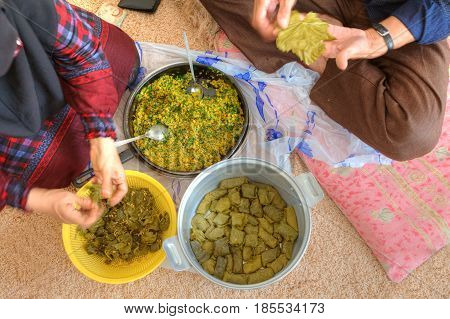 Bandar Abbas Hormozgan Province Iran - 15 april 2017: Man and woman cooking a dish of Persian cuisine Stuffed Grape Leaves or dolmeh.