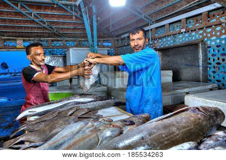 Bandar Abbas Hormozgan Province Iran - 15 april 2017: Iranian fishmonger passes assistant fresh flounder on the covered fish market.
