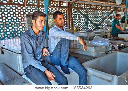 Bandar Abbas Hormozgan Province Iran - 16 april 2017: Two Iranian men sit on boxes near the entrance to the indoor fish market.