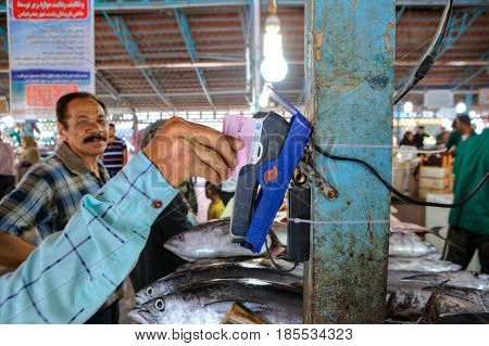 Bandar Abbas Hormozgan Province Iran - 16 april 2017: Payment for purchases on the fish market using a mobile terminal for credit cards.