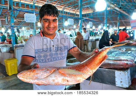 Bandar Abbas Hormozgan Province Iran - 16 april 2017: An Iranian man shows a large fish in a covered fish market.
