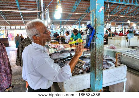 Bandar Abbas Hormozgan Province Iran - 16 april 2017: The Iranian man uses a mobile terminal to pay for purchases in the fish market.