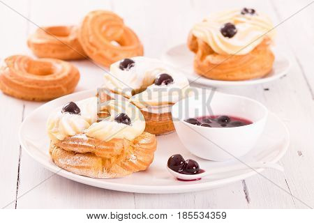 Zeppole with pastry cream on white dish.