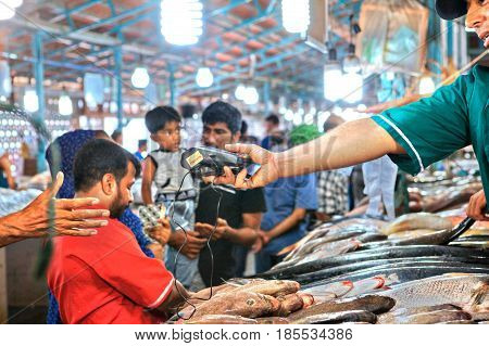 Bandar Abbas Hormozgan Province Iran - 16 april 2017: The seller of the fish market gives the assistant a mobile terminal for reading credit cards.