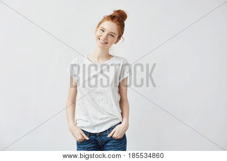 Young attractive redhead girl smiling looking at camera. Isolated on white background. Copy space.