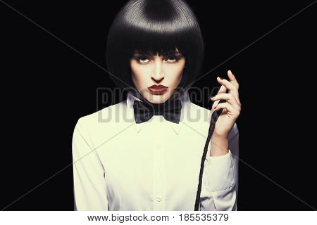 Sexy dominatrix in wig and red lips posing with whip color graded isolated on black
