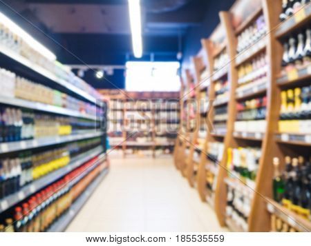 Defocused blur of supermarket aisle with shelves of alcohol drinks. Blur background with bokeh. Defocused image