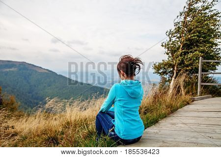 The young girl sits on a mountaintop. The concept of travel and lifestyle.