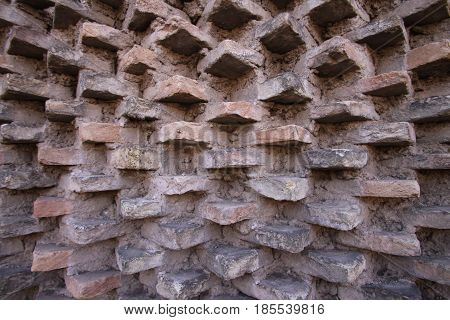 Interesting bricks protrude out of a brick and mortar wall
