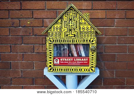 SYDNEY AUSTRALIA - MAY 01 2017: Street library in the form of a little yellow booth with free books. Horizontal shot of a library exchange.