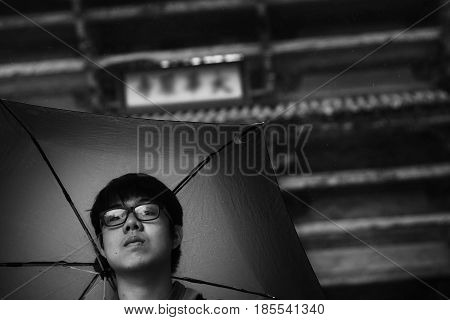 Black and white view of travelling Japanese cultural tourism of tourist In times of rain using the umbrella Openning during travel at Todaiji Temple Nara Japan.