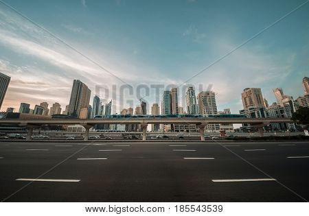 Moving Dubai metro train on the bridge against upscale community skyline.