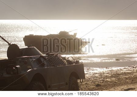 A Military Tank Rides The Water At Sea, Scattering Water Splashes, A Sunny Evening