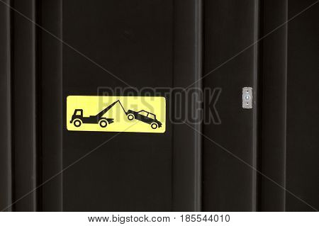 Yelow sign on black garage door - traffic sign - no parking tow away zone sign