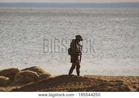 Military Soldier On The Beach Near The Water's Edge
