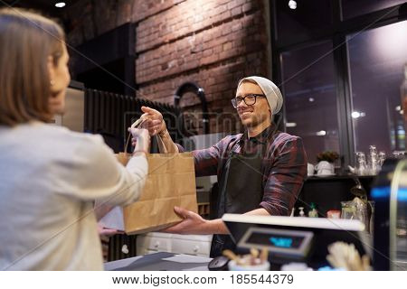 small business, food, people and service concept - happy female customer taking paper bag from man or barman at vegan cafe