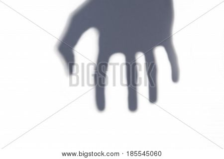 Grasping mysterious hand shadow on white background.