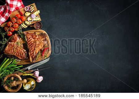 Grilled T-bone steaks with fresh herbs and vegetables on dark background