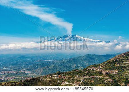 Smoking Mount Etna Volcano as seen from Taormina, Sicily, Italy