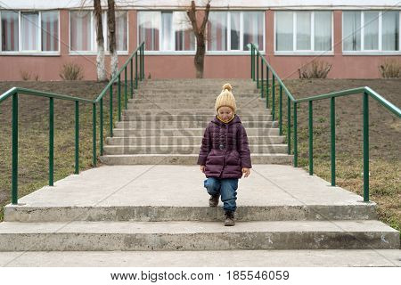 Little girl in a violet coat and a beige woolen hat staying on the stairs and smilling.