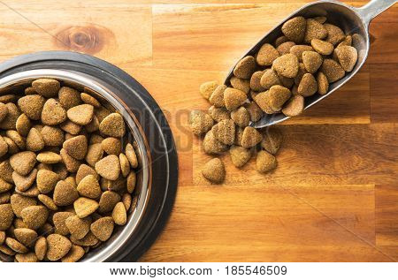 Dry kibble dog food in metalscoop on wooden table. Top view.