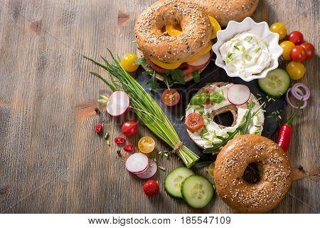 Vegetarian bagel sandwich with cream cheese fresh veggies and arugula healthy food lunch breakfast snack