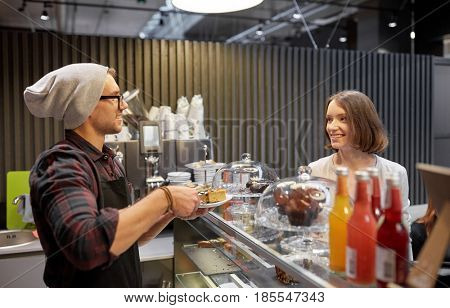 small business, food, people and service concept - happy man or barman with cake serving female customer at vegan cafe