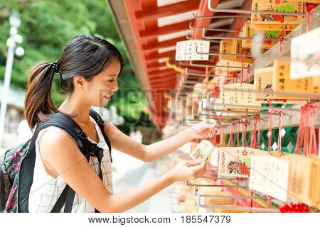 Woman hanging the wishes in Japanese temple