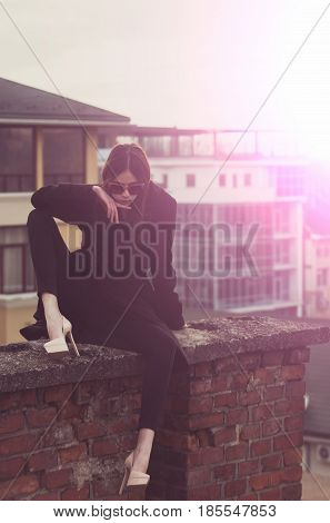 Pretty girl or beautiful woman in vintage sunglasses fashionable black coat and elegant beige shoes on high heels sitting on red brick fence on sunny day on urban background. Modern fashion and style