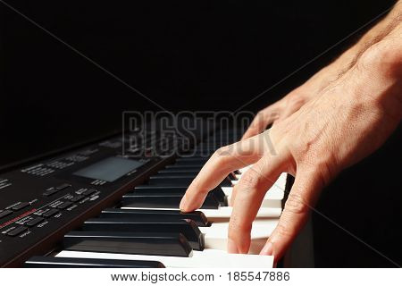 Hands of musician playing the electronic synth on a black background