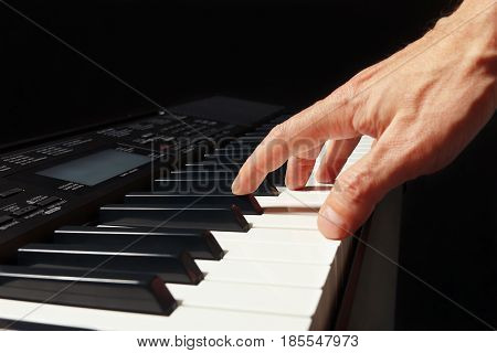 Hand of pianist playing the synthesizer on a black background