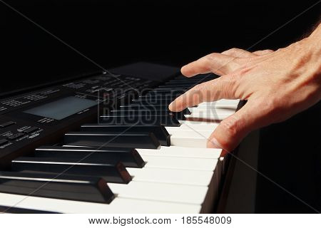 Hand of pianist playing the electronic piano on a black background