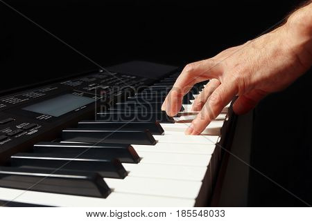 Hand of pianist playing the electronic synth on a black background