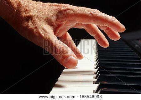 Hand of pianist play the keys of the electronic piano on a black background close up