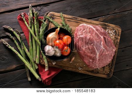 Fresh beef tenderloin with vegetables on a kitchen board on a dark wooden table top view. Ingredients for cooking healthy food