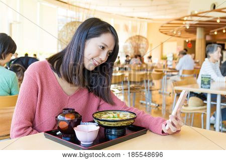 Woman making a video call on cellphone in Japanese restaurant