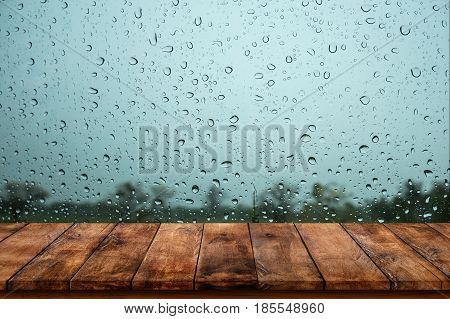 Wood table with rain water drop on glass background.