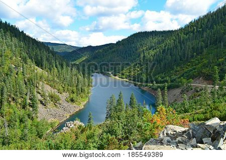 Between the hillock and the rock there is a mountain lake, a beautiful view of the forest and the taiga, the blue sky is the cessation of this lake