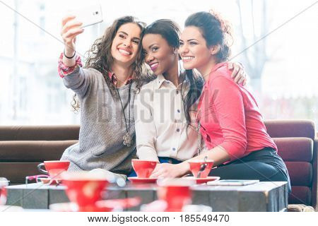 Young women in cafe taking a selfie of themselves drinking coffee with Smartphone