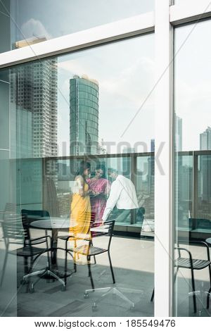 Proficient Indian business people at work in a modern office building with panoramic city view