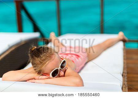 Little girl enjoying tropical summer vacation relaxing at overwater villa in luxury resort
