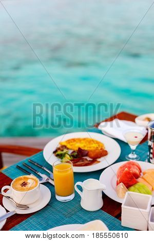 Delicious organic fruits, eggs, juice and coffee served for breakfast at tropical ocean edge in a luxury resort
