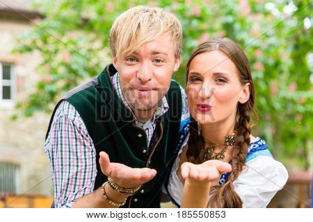 Couple wearing Bavarian clothes blows a kiss from a beer garden