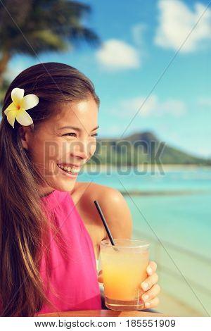 woman drinking mai tai drink at outdoor bar on Waikiki beach, Honolulu, Oahu, Hawaii. Asian girl enjoying sunset evening, luxury travel lifestyle.