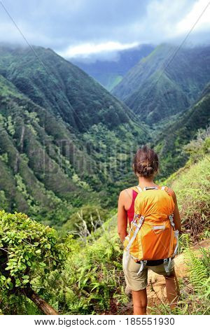 Hiker woman backpacker hiking with backpack in Hawaii mountains on Waihee ridge trail, Maui, USA. Hiker girl walking in tropical forest nature landscape.