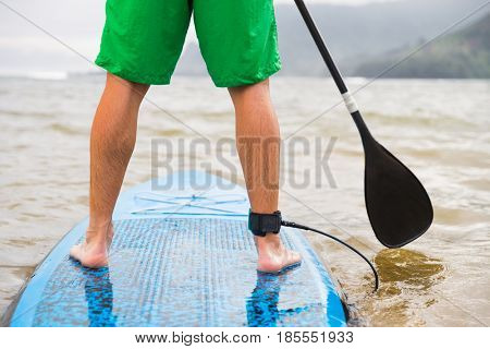 Paddleboard man paddling on SUP stand up paddle board on lake. Closeup of feet and legs.