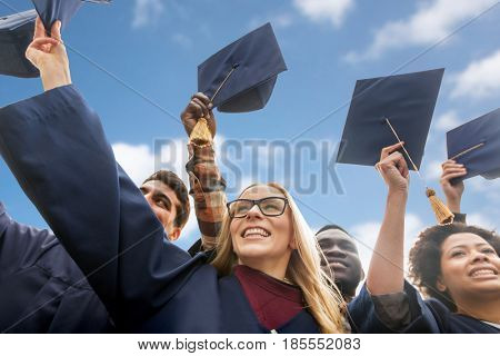 education, graduation and people concept - group of happy international students in bachelor gowns waving mortar boards or hats over blue sky and clouds background