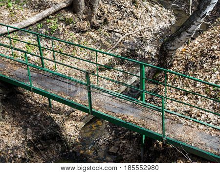 Wooden bridge over a forest stream. Iron railings. View from above. Horizontal photo.