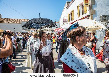 Saintes-Maries-de-la-Mer, France - May 25, 2015. Religious feast in honor of the Holy Maries in Provence. Women in vintage dresses and with umbrellas. The concept of ethnographic tourism