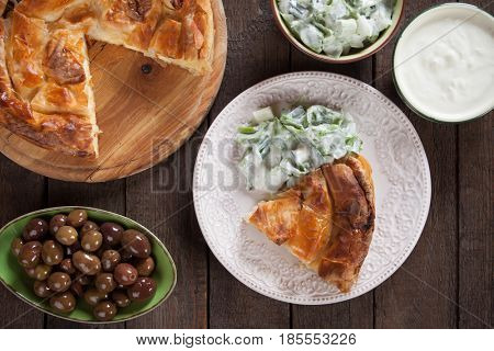 Phyllo pastry cheese pie with yogurt, salad and olives
